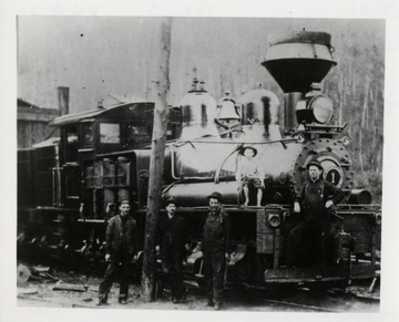 Four men and a boy pose beside and on a train engine.