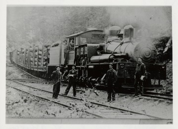 Train engine with log carts.  Two men in engine, four men standing by tracks.