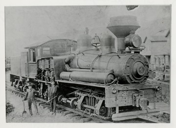 Train engine with two men beside of it.