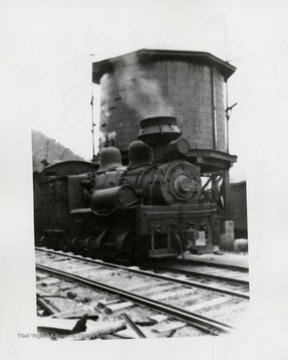 Shay train engine in front of a water tank.