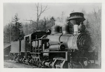 Front view of a Shay train engine with forest in the background.