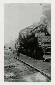 Front view of Shay train engine.  Man standing beside of it.
