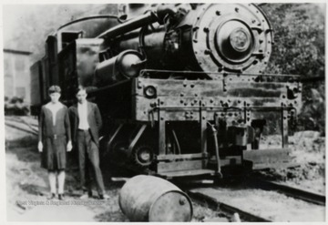 Man and girl standing beside a Shay train engine.