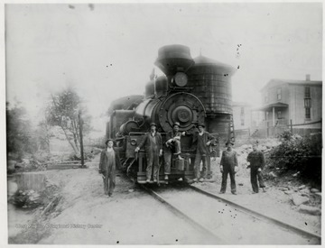 Front view of Shay No. 11 train engine at the water tank with six crew members in front.