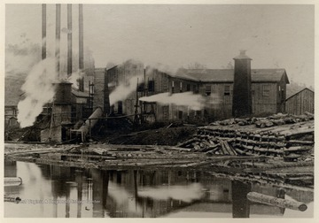 Lumber mill in operation on edge of log pond.