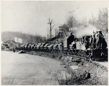 Men stand on a Shay locomotive hauling a train of cars filled with logs.
