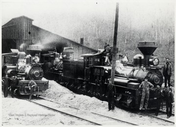 Men standing in front, on, and around the locomotives.