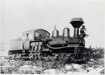 Shay train engine.  Construction camp.  At throttle:  Charlie Crommer.  In doorway:  Unknown