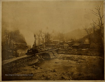 Shay locomotive and fully loaded log cars on a bridge over the Cherry River in Nicholas County, W. Va.