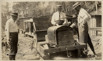 "C.H. Holden, of Parkersburg, C.W. Sprinkle, of Cincinnati, and Dave Cougar, of Skelt, W.Va. checking a Model ""T"" converted for use on the Pickens and Webster Spring Railroad."