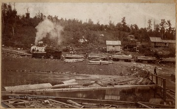 The Jacob L. Rumbarger Lumber Company Shay No. 1 hauling log cars. Crew rolls logs into the water from the train.