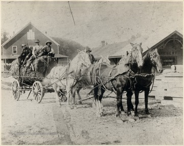 Four horses pulling a large log.   Neither the store nor the railroad building are still standing today.