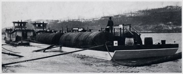 Barge carrying oil storage tanks.  Man standing in between the tanks.