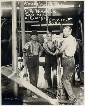 Three men changing bits on an oil well drilling rig.