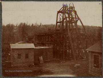 A hoist mechanism for a shaft coal mine next to several buildings at a mine in an unknown location, likely in West Virginia.