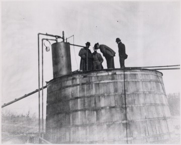 Men standing on top of an oil tank