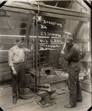 Two men forging a drill bit, one holding chain, one raising hammer.