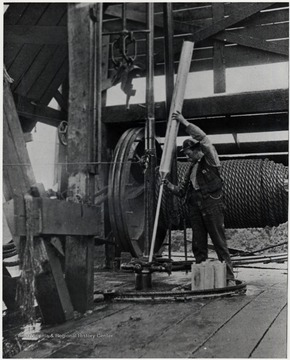 Man working with a piece of oil machinery.