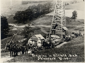 Teams of horses hauling supplies by a derrick.