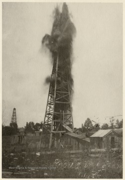Large amounts of oil shooting out of a derrick after being shot with nitroglycerin.