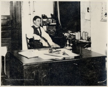 The late Fred Smith sitting at a desk.