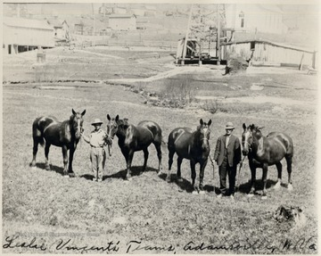 Two men standing with four horses.  Oil well in background.