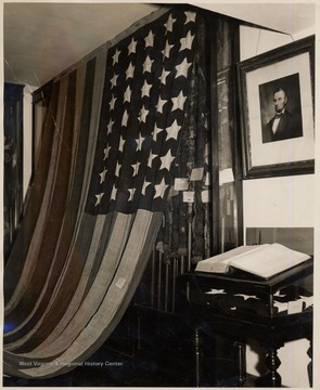 Old American Flag hanging on a wall beside a picture of Abraham Lincoln.The Flag was hand sewn in Shepherdstown within days of West Virginia's creation on June 20, 1863. It is one of only a few 35-star flags in existence. The 35-star flag was in use for only three years, and during most of its lifespan was not recognized by the southern states represented among its stars.<br />