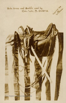 Side Arms and Saddle used by Colonel Wm. B. Curtis.  Items resting on an American Flag.  Copyright 1908 by W.T. Nicoll.