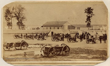 Wagons and cannons parked at an encampment. Note the laundry hanging on a caisson in the foreground.