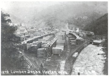 Lumber docks in Horton, W. Va. next to train tracks and river.