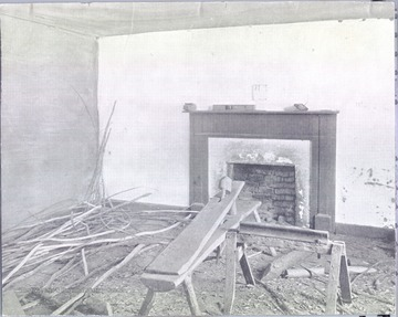 Interior of the deserted room in which Stonewall Jackson died, Guinea Station, VA. Fireplace, saw horse and scattered pieces of wood are visible.