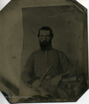 Bearded man wearing a dress uniform with dark trim, of a Confederate officer, and holding a sword.