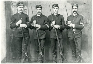 Four soldiers from the Zickafoose family pose for a portrait holding muzzle-loading rifles with bayonets fixed.