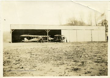 "Preparing to start aircraft #1 Curtiss JN-4 and ""grass cutter"" training plane. Plane #1 was destroyed in a crash on August 4, 1917.  In this crash Cadet C.B. Lambert (of Welch, West Virginia) was killed, and Lieutenant William Frey was injured.  (See newspaper Wheeling Register, August 4, 1917.)  Each ground crewman in the picture is about to ""turn over the prop"" in order to start the engines of the airplanes."
