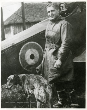 Lt. Louis Bennett, Jr. and dog standing in front of S. E. 5a airplane.