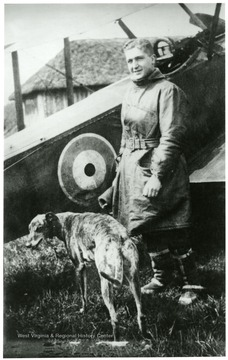 Lt. Louis Bennett, Jr. and dog standing in front of a S. E. 5a airplane.