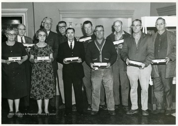 Group portrait of glass workers. From left to right, Front Row: Della Burckett, Cythia Dunlap, Bruce Montgomery, Albert Wheeler, Floyd Carney, Cecil Coffield; Back Row: Eldon Fox, Michael Grubber, Orville Bickerton, Norman Greenan, James Pelley.