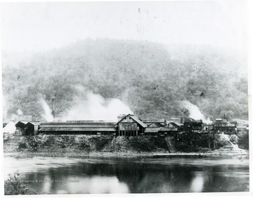 View of Dickinson Salt Works from opposite bank of Kanawha River. Made about 1910. This is the only picture in existance showing salt loaded on barge for ferrying across river where it was loaded on C&O Railroad. The New York Central Railroad had served the plant for years before this picture was taken, but due to higher freight rates by the NYC, it was still possible to ship by C&O to some points at a saving.