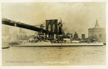 Postcard of the U.S.S. West Virginia going under the Brooklyn Bridge.