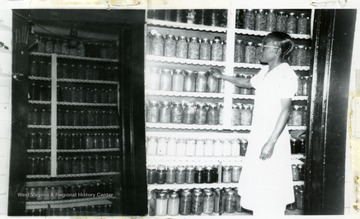 Bridget, an African-American Extension Service worker, displays shelves of canned Faraday food.