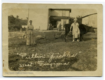 Two women and a cow in front of a house.  Handwritten note on back says, 'Golda Woodward Compliments and best wishes of your cousin Freed [sic] Gage, Okla. June 20, 1915.'