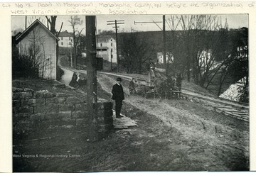 Picture of Cut No. 18 road in Morgantown, Monongalia County, W. Va. before the organization of W. Va. Good Roads Association. Picture has one man standing on the side walk and another man driving a horse drawn wagon in the street. From the Report of the W. Va. State Board of Agriculture for the Quarter Ending Sept. 30, 1908