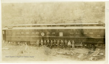 Group portrait taken at Thomas, W. Va. of a group of miners standing next to a Department of the Interior Bureau of Mines Train.