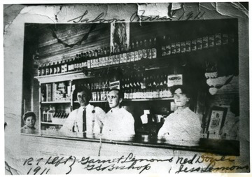 A child and three men stand behind the bar in this saloon.