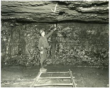 A man stands in the mining shaft holding an instrument to test the gas levels in the mine.