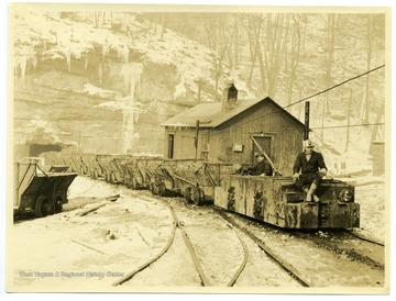 Two miners riding a electric locomotive outside of a mine during the winter.