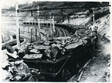 This trip of loaded cars contain mine run coal, ready to be dumped, that 'White Oak' is proud to put its trade mark on as a stamp of approval. It has received every care in mining, shooting and transportation that can possibly be given any coal up to the point where it is ready to be sized and loaded into railroad cars. This coal, due to careful shooting, is not friable but firm and will handle in railroad cars through to destination with minimum of degradation.