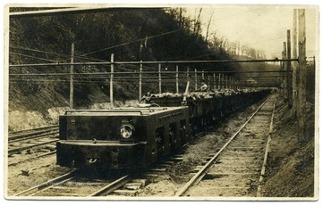 Postcard of an electric locomotive carrying coal and miners.
