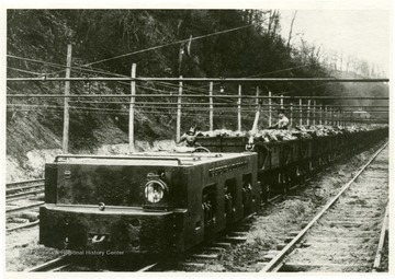 An electric locomotive carrying coal and miners outside of the mine.