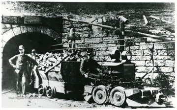 Miners standing next to coal carts and a locomotive. John Williams/Coal Life Project.